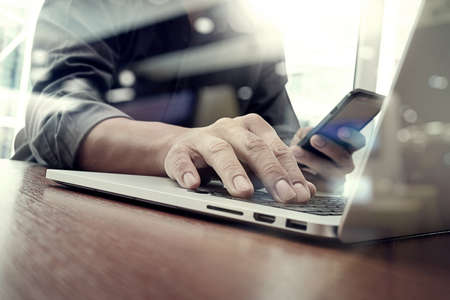 smart investing: designer hand working and smart phone and laptop on wooden desk in office with london city background Stock Photo