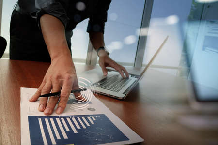 economic: business documents on office table with smart phone and digital tablet and graph business diagram and man working in the background