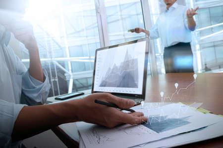 revisando documentos: documentos de negocios en la mesa de la oficina con el teléfono inteligente y el ordenador portátil y el negocio gráfico con el diagrama de la red social y dos colegas en discusiones datos en segundo plano