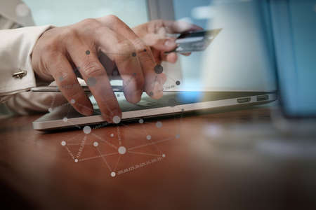 internet security: close up of hands using laptop and holding credit card with social media diagram as Online shopping concept Stock Photo
