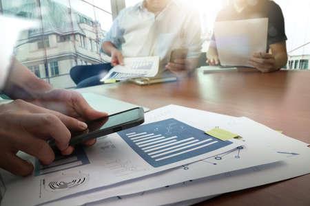 reuniones empresariales: de trabajo de mano del dise�ador y el tel�fono inteligente y port�til de escritorio de madera en la oficina y dos colegas en discusiones sobre los datos con el fondo de la ciudad de Londres