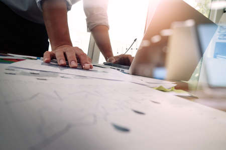 Doble exposición de la mano de negocios que trabaja con la nueva estrategia de la computadora y los negocios modernos como concepto