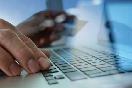 electronic: close up of hands using laptop and holding credit card as Online shopping concept