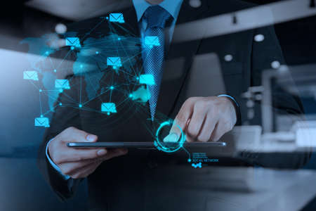 mobile phones: double exposure of businessman hand using tablet computer shows social network concept Stock Photo