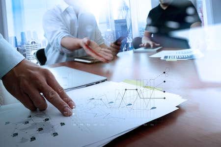 스마트 전화 및 노트북 컴퓨터 및 그래프 office 테이블에 비즈니스 문서 소셜 네트워크 다이어그램 및 백그라운드에서 데이터를 논의하는 두 동료와 비