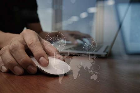 木製の机の上のノート パソコンに取り組んでいるビジネス人間手のクローズ アップ 写真素材