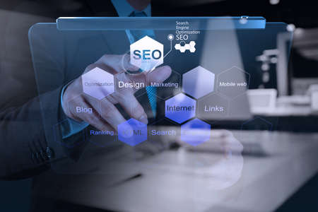 website words: double exposure of businessman hand showing search engine optimization SEO as concept