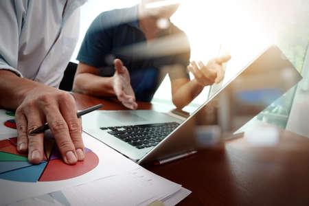 recursos financieros: documentos de negocios en la mesa de la oficina con el teléfono inteligente y el ordenador portátil y el negocio gráfico con el diagrama de la red social y dos colegas en discusiones datos en segundo plano