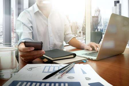 개념으로 나무 책상에 새로운 현대적인 컴퓨터와 스마트 폰 및 사업 전략 작업 사업가 손