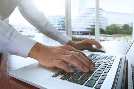 negocio internacional: la mano de negocios que trabajan con documentos de negocios en la mesa de oficina con el ordenador port�til y la ciudad de Londres fondo borroso Foto de archivo