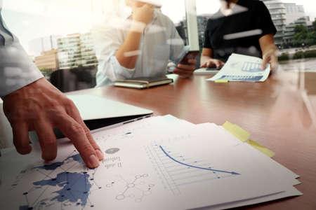 documents d'affaires sur la table de bureau avec téléphone intelligent et l'ordinateur portable et d'affaires graphe avec le diagramme de réseau social et de deux de ses collègues dans le forum de données en arrière-plan