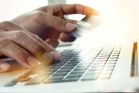 ノート パソコンを使用し、オンライン ショッピングのコンセプトとしてクレジット カードの手のクローズ アップ