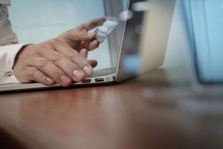 entering information: close up of hands using laptop and holding credit card as Online shopping concept