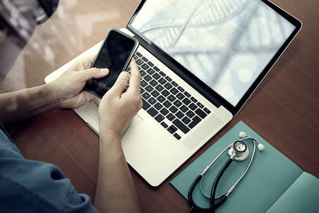 의료 개념으로 나무 책상에 소셜 미디어 네트워크와 현대 컴퓨터와 스마트 폰 작업 의학 의사 손의 평면도 스톡 콘텐츠