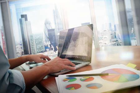 スマート携帯電話およびラップトップ コンピューターとグラフのビジネス社会ネットワーク ダイアグラムとバック グラウンドで働いていた男のオ