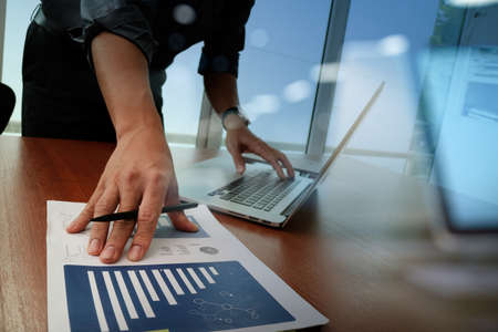 digital: business documents on office table with smart phone and digital tablet and graph business diagram and man working in the background