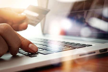 cerca de las manos usando la computadora portátil y la celebración de tarjeta de crédito como el concepto de compra en línea Foto de archivo