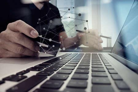 stretta di mano con il computer portatile e la carta di credito come concetto di shopping online