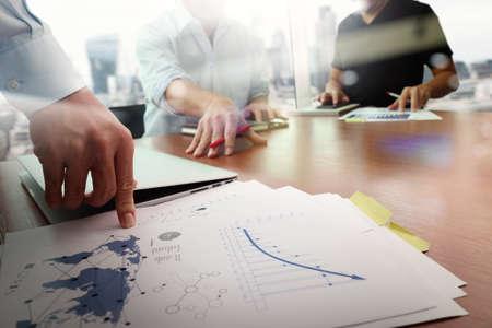 Geschäftsunterlagen auf Büro-Tabelle mit Smartphone und Laptop-Computer und Grafik Geschäft mit sozialen Netzwerkdiagramm und zwei Kollegen diskutieren im Hintergrund Daten