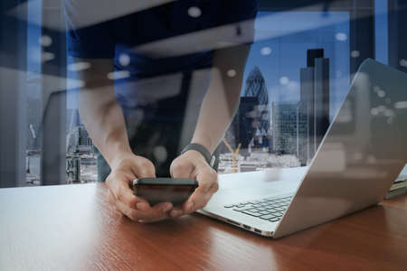 mobile marketing: businessman hand working with new modern computer and smart phone and business strategy on wooden desk as concept Stock Photo