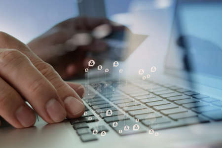 close up of hands using laptop and holding credit card with social media diagram as Online shopping concept Stock Photo