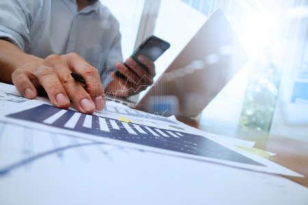 Geschäftsunterlagen auf Büro-Tabelle mit Smartphone und Laptop-Computer und Grafik Geschäft mit sozialen Netzwerkdiagramm und Mann arbeitet im Hintergrund