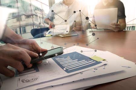 homme d'affaires travaillant main avec nouvel ordinateur moderne et téléphone et la stratégie d'entreprise intelligente et deux de ses collègues dans le forum de données sur le bureau en bois que le concept Banque d'images