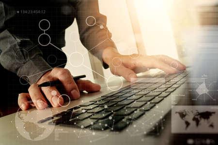 Gros plan de l'homme d'affaires travaillant main avec des couches d'affaires ordinateur portable schéma numérique sur le bureau en bois que le concept