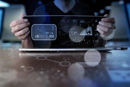 comunicación: Hombre de negocios de la mano de trabajo en el ordenador portátil con la estrategia de negocio de la capa digital y diagrama de los medios sociales en el escritorio de madera Foto de archivo