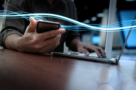 business technology: Waves of blue light and businessman using on smartphone and laptop computer as concept Stock Photo
