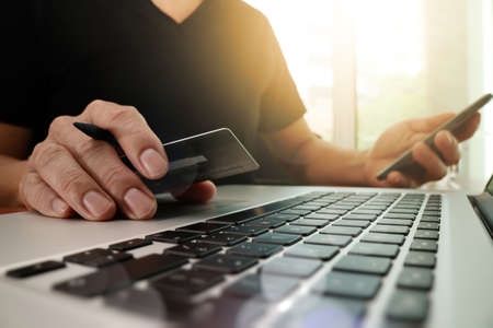 mani con il computer portatile e in possesso di carta di credito con schema social media come concetto di shopping online