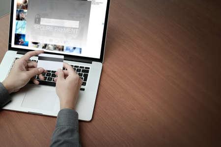 """vue de dessus des mains utilisant un ordinateur portable et la tenue carte de crédit avec """"Paiement sécurisé"""" sur l'écran comme concept de boutiques en ligne"""