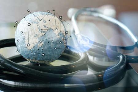 Studio-Makro von einem Stethoskop und Textur Globus mit digitalen Tablette als medizinisches Netzwerk-Konzept