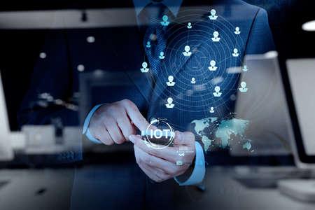redes de mercadeo: doble exposición de la mano mostrando Internet de las cosas (IoT) Diagrama de palabra como concepto
