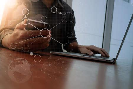 mano progettista di lavoro e di smart phone e computer portatile con lo schema dei social media sulla scrivania in legno in ufficio