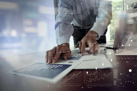 ビジネス グラフ情報図の概念としての木製机の上でラップトップ コンピューターに取り組んでビジネス人間手のクローズ アップ