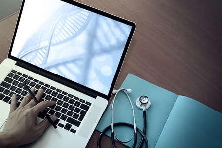 informe: vista superior de Medicina de la mano del médico de trabajo con efectos ordenador y capa de ADN moderno en escritorio de madera como concepto médico