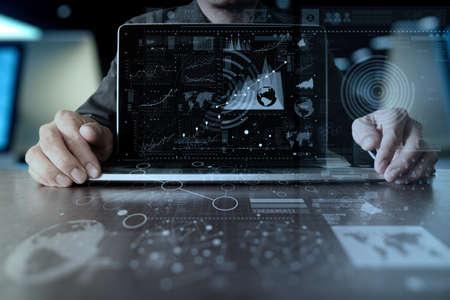 man mano d'affari di lavoro sul computer portatile con la strategia di strato di business digitale e schema dei social media sulla scrivania di legno Archivio Fotografico