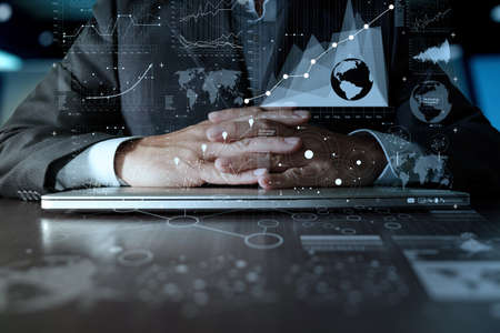 big data: business man hand working on laptop computer with digital layer business strategy and social media diagram on wooden desk Stock Photo