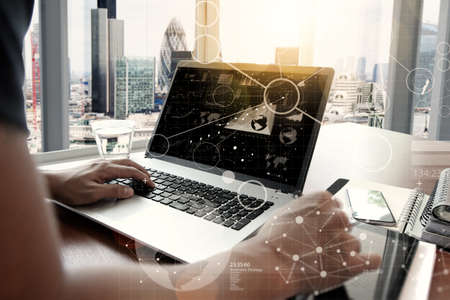 business documents on office table with smart phone and digital tablet and graph business with social network diagram and man working in the background Stockfoto