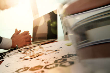 símbolo de la medicina: Medicina mano del m�dico trabaja con la computadora moderna y el tel�fono inteligente en el escritorio de madera como concepto m�dico
