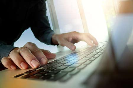 Cierre para arriba del hombre de negocios mano trabajando en equipo portátil pantalla en blanco en el escritorio de madera como concepto