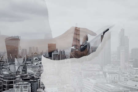 BUSINESSMEN: Double exposure of success businessman using digital tablet with london building and social media diagram