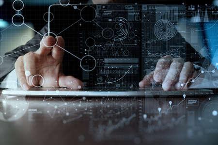 Geschäftsmann Hand auf Laptop-Computer mit Digitalschicht die Geschäftsstrategie und Social-Media-Diagramm auf Holz-Schreibtisch