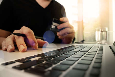 hands using laptop and holding credit card with social media diagram as Online shopping concept