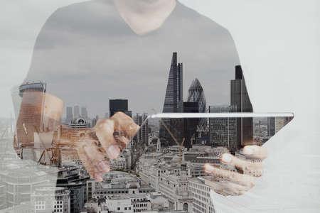 Doppelbelichtung von Erfolg Geschäftsmann unter Verwendung der digitalen Tablette mit London Gebäude und Social Media-Diagramm
