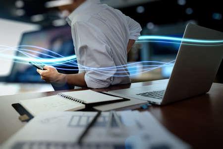 Onde di luce blu e uomo d'affari con su smartphone e computer portatile come concetto