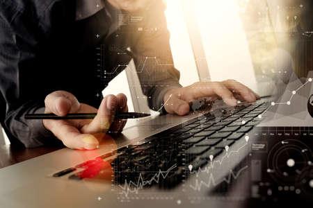 Primer plano de la mano del hombre de negocios que trabaja enCon ordenador capas empresariales diagrama portátil digital en el escritorio de madera como concepto