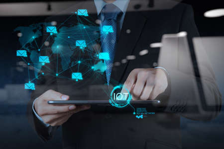 double exposure of hand showing Internet of things (IoT) word diagram as concept Standard-Bild