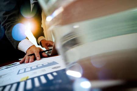 papeles oficina: hombre de negocios de la mano de trabajo en el ordenador port�til con el diagrama de informaci�n de gr�fico de negocios en el escritorio de madera como concepto